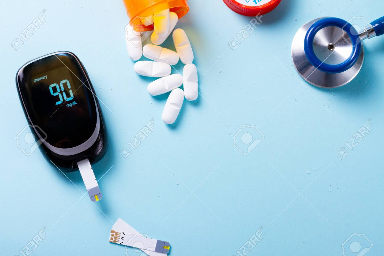 White pills in orange bottle with blood glucose meter on blue with copy space - 111498487