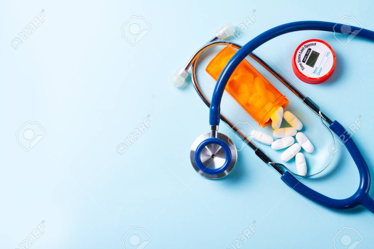 White pills in orange bottle with stethoscope on blue with copy space - 111498491
