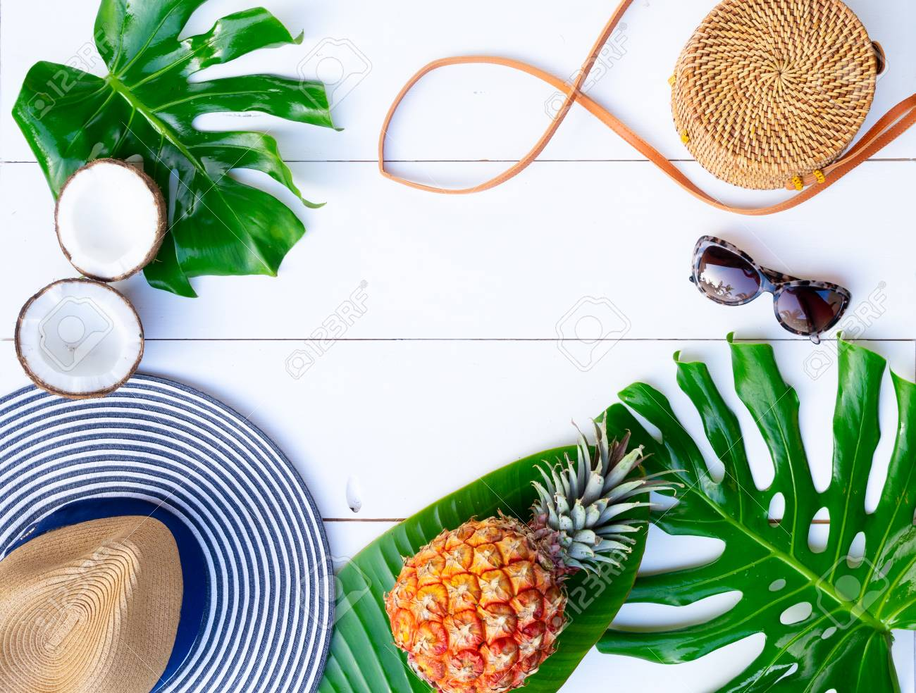 Summer flat lay frame with hat, bag, leaves and fruits on white background with copy space - 120867428