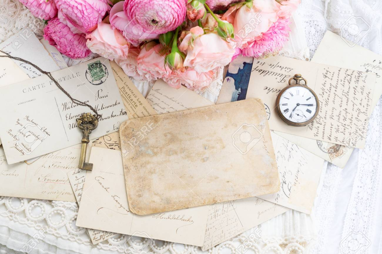 Pink and white roses and ranunculus with antique clock and skeletone key, copy space on vintage letter - 124708096