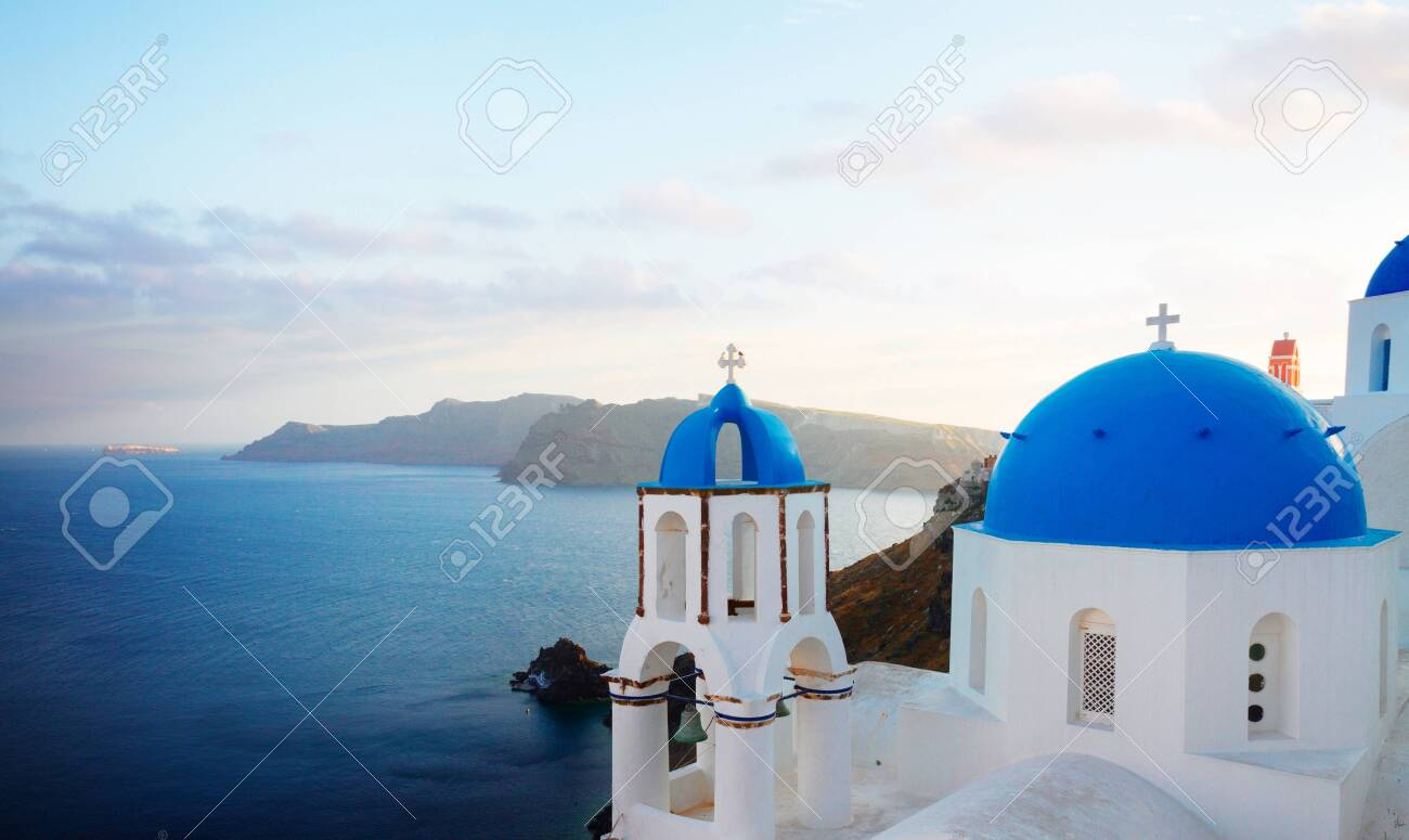 traditional greek village Oia of Santorini, with blue domes of churches in sunset light, Greece, panorama - 149869731