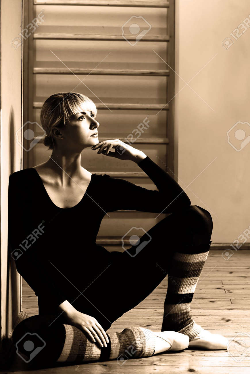 Beautiful ballet dancer sitting on a floor and relaxing after exercise Stock Photo - 2378655