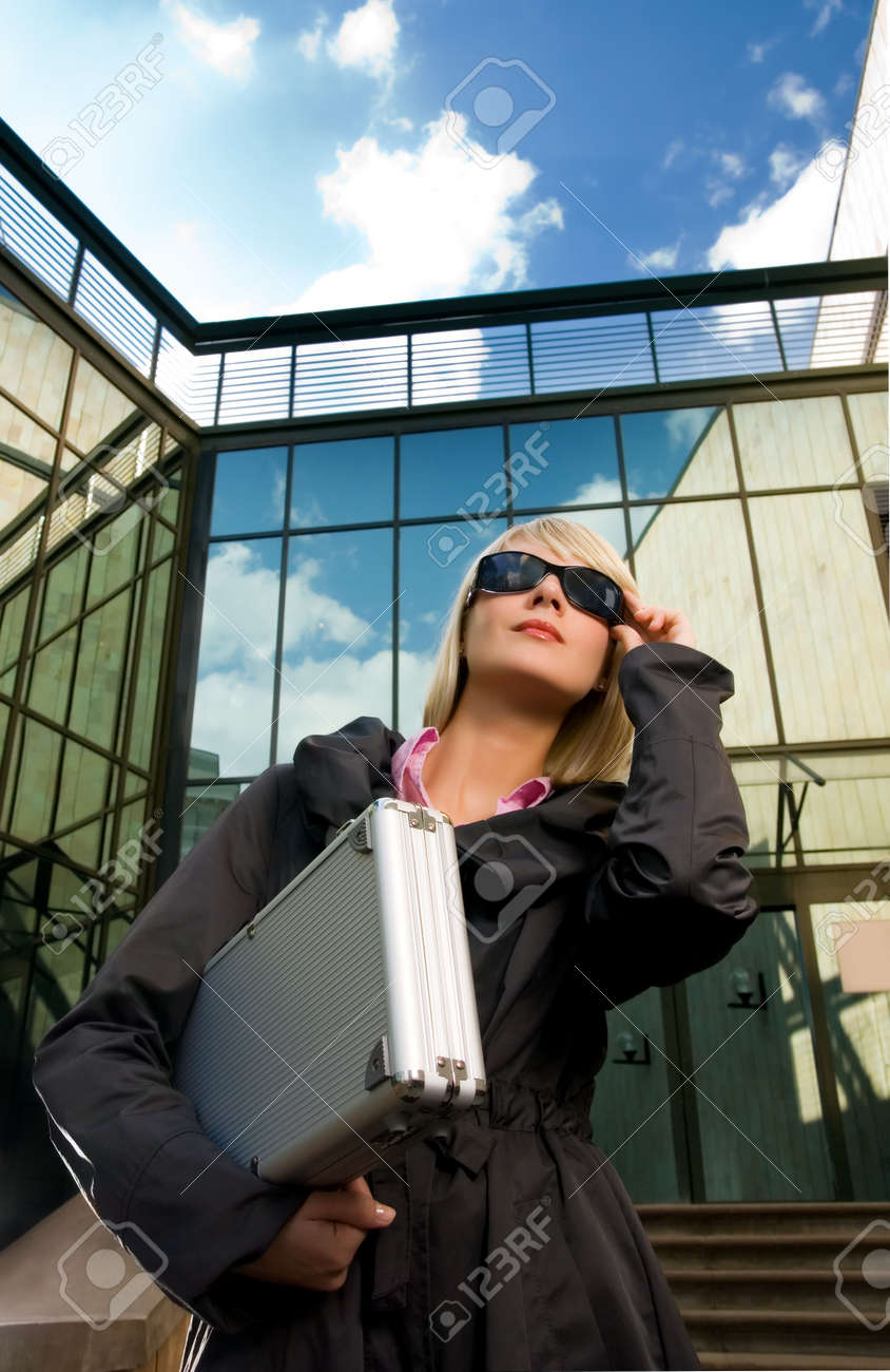 Beautiful young woman with silver case near the modern office building Stock Photo - 2948976