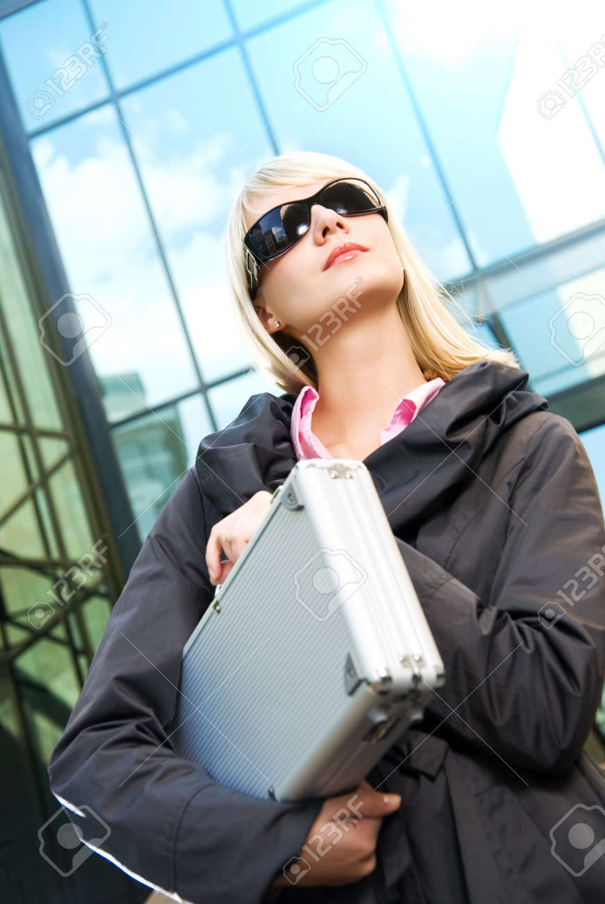 Beautiful young woman with silver case near the modern office building Stock Photo - 3025290