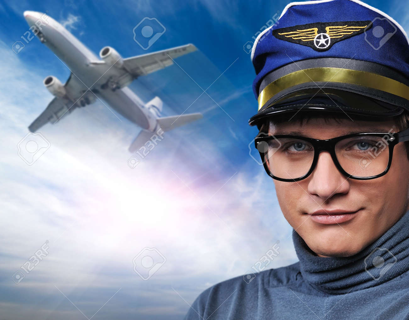 Handsome young pilot against flying plane Stock Photo - 6452970