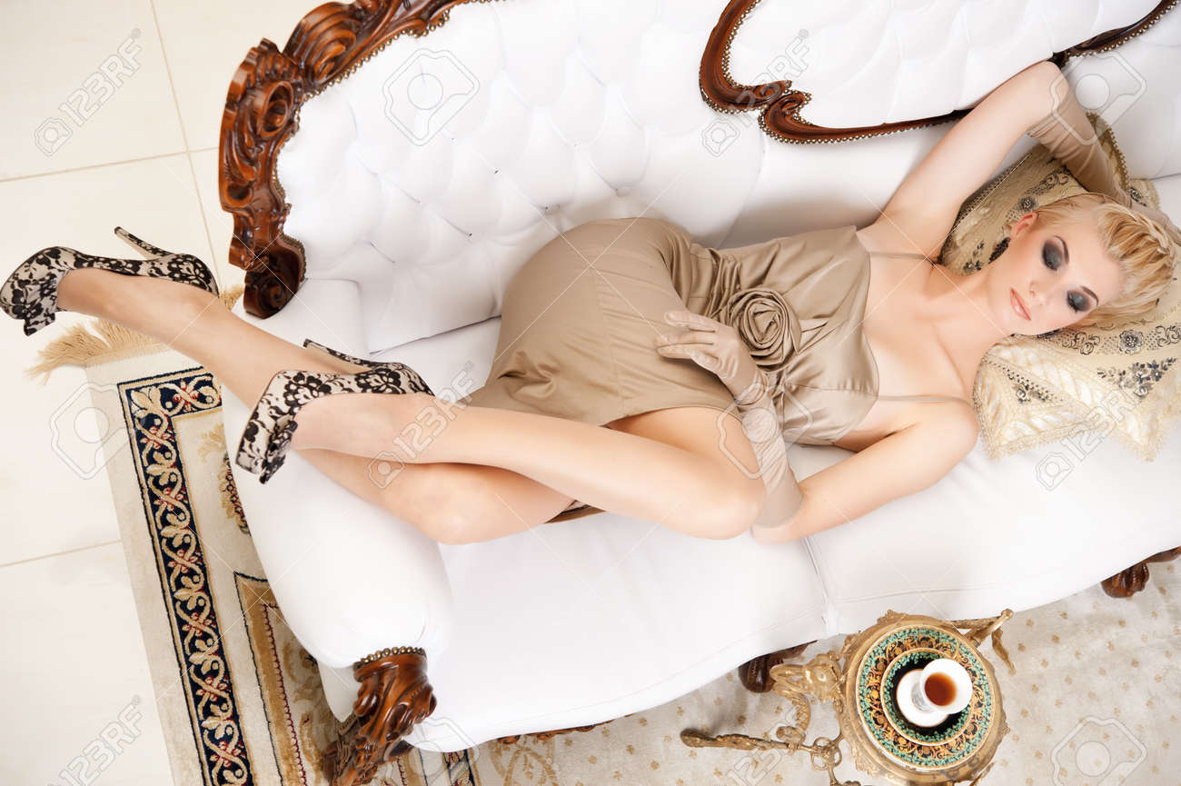 Блондинка лежит на диване