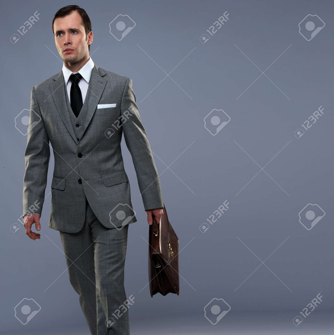 Businessman with a briefcase isolated on grey Stock Photo - 14078348