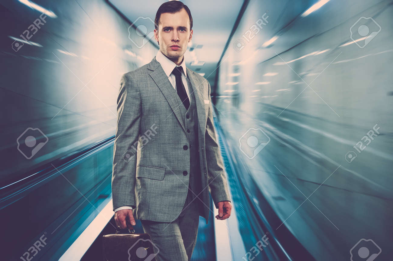 Man in classic grey suit with briefcase standing on escalator - 16086481