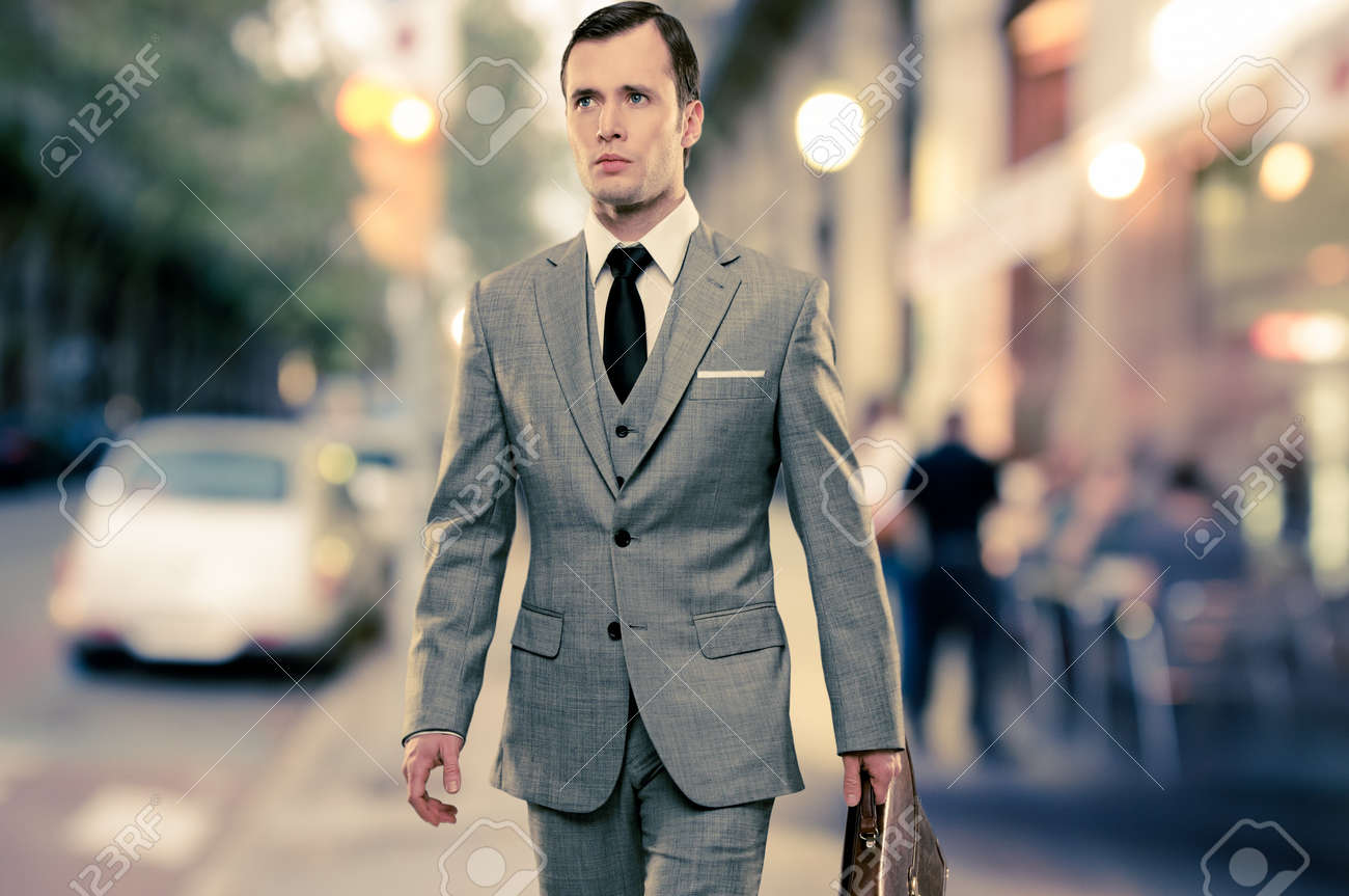 Man in classic grey suit with briefcase walking outdoors Stock Photo - 16304867