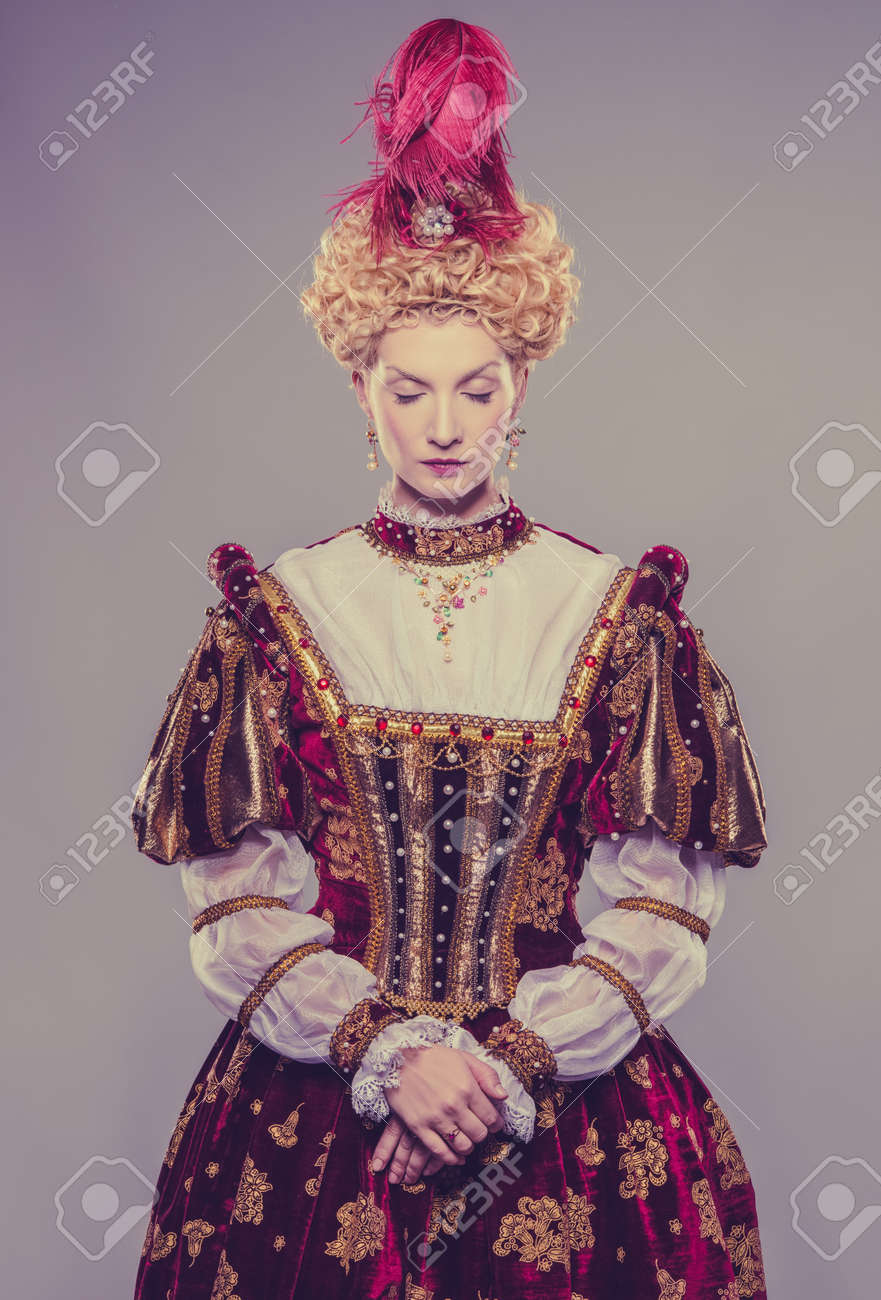 Haughty queen in royal dress isolated on grey Stock Photo - 17507823