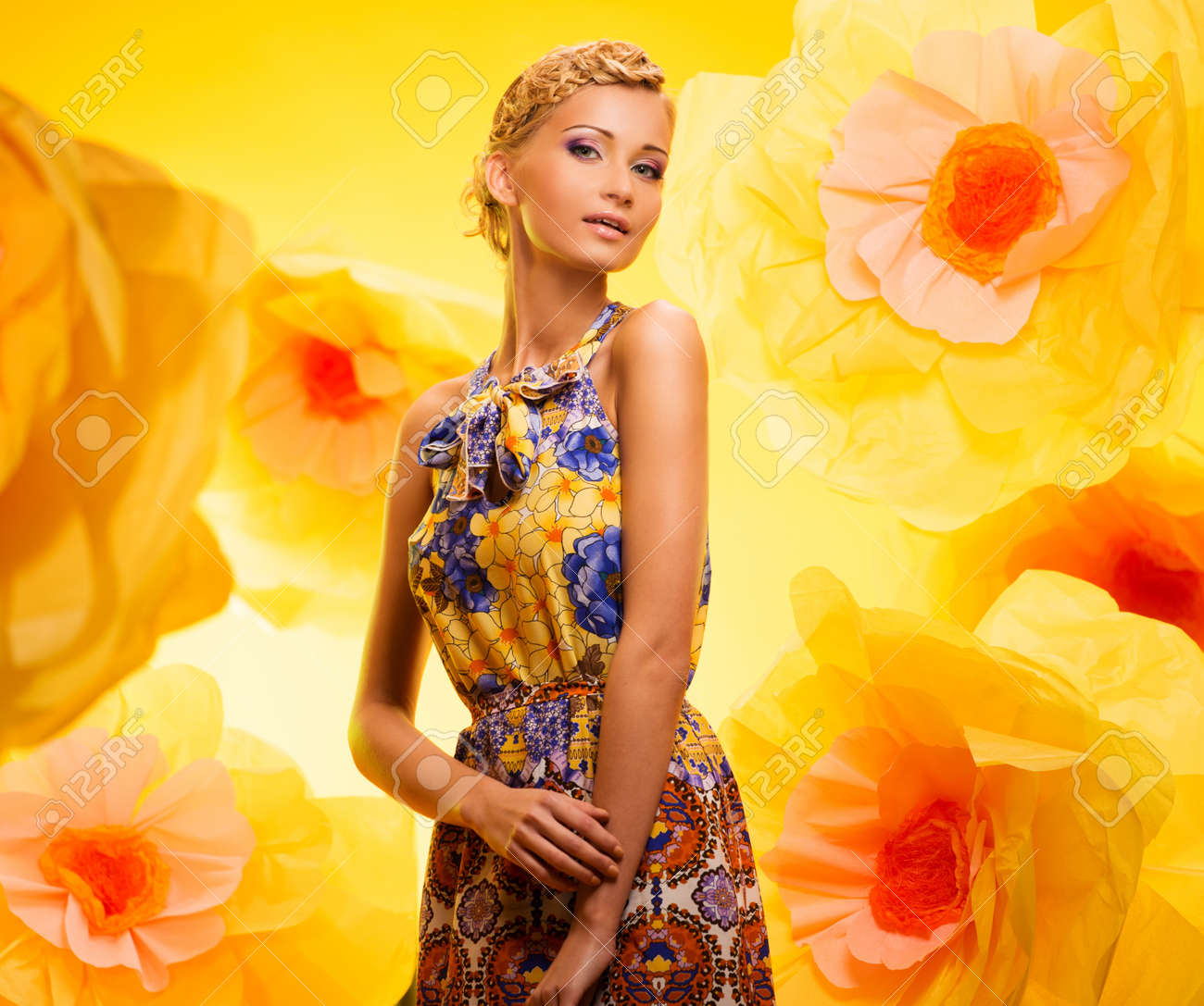 Beautiful young blond woman in colourful dress among big yellow flowers Stock Photo - 19225031