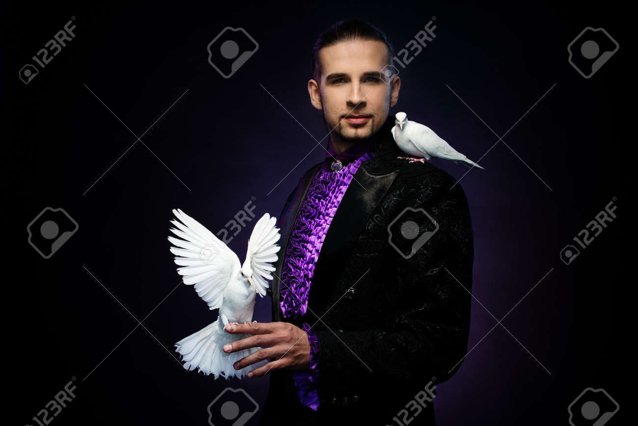Young handsome brunette magician man in stage costume with his trained white doves Stock Photo - 19913068