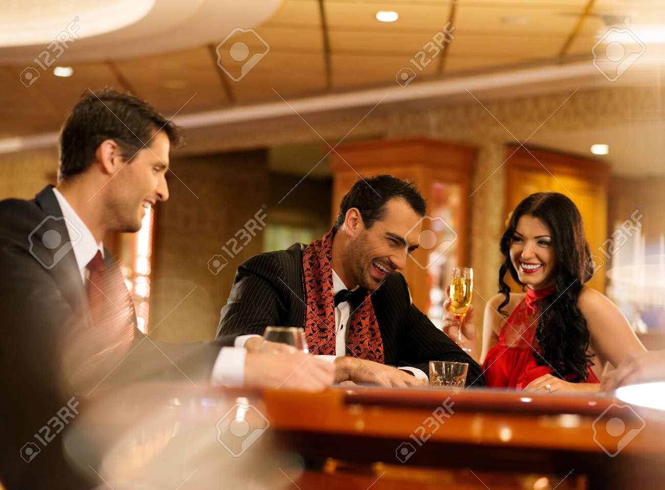 Happy young people sitting with drinks behind table Stock Photo - 20046791