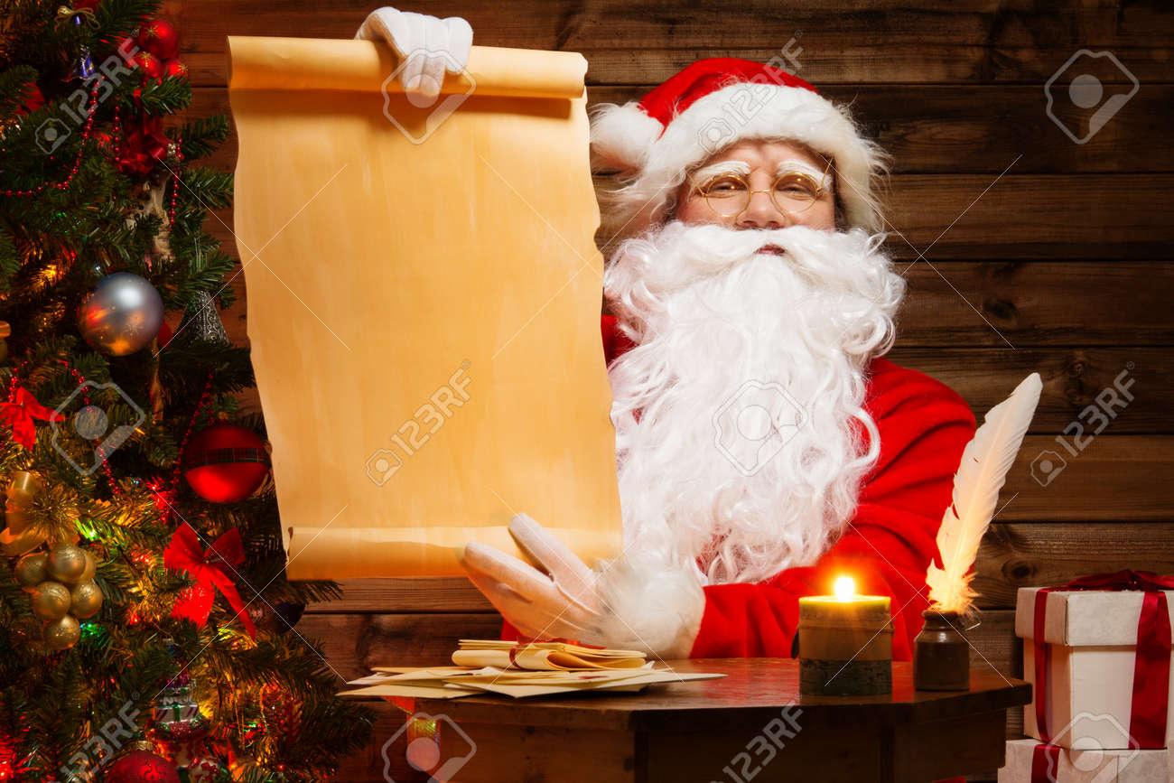 Santa Claus In Wooden Home Interior Holding Blank Wish List Scroll – Santa Wish List Online