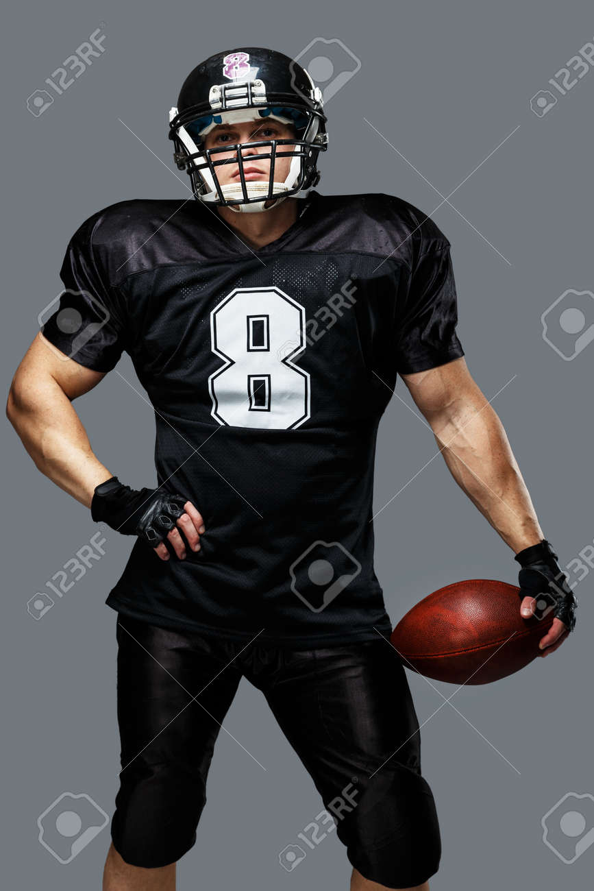 american football player with ball wearing helmet and jersey stock