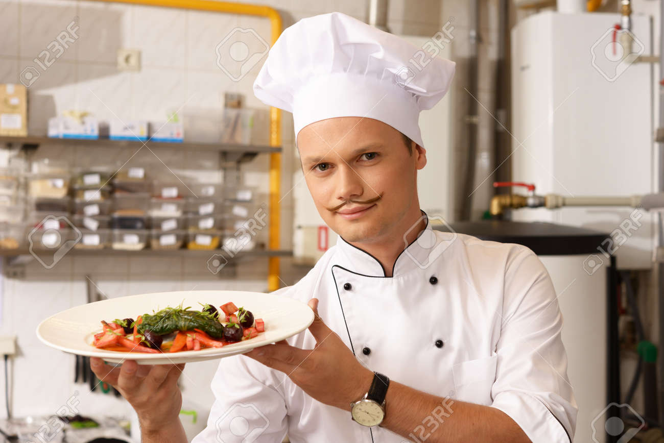 young chief cook with gourmet food on kitchen in restaurant stock