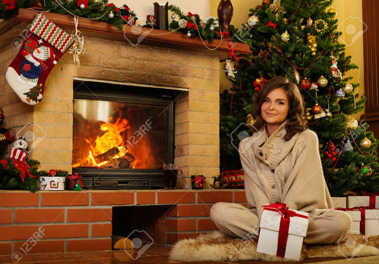 Christmas house interior - Stock Photo Young Woman Near Fireplace In Christmas Decorated House Interior