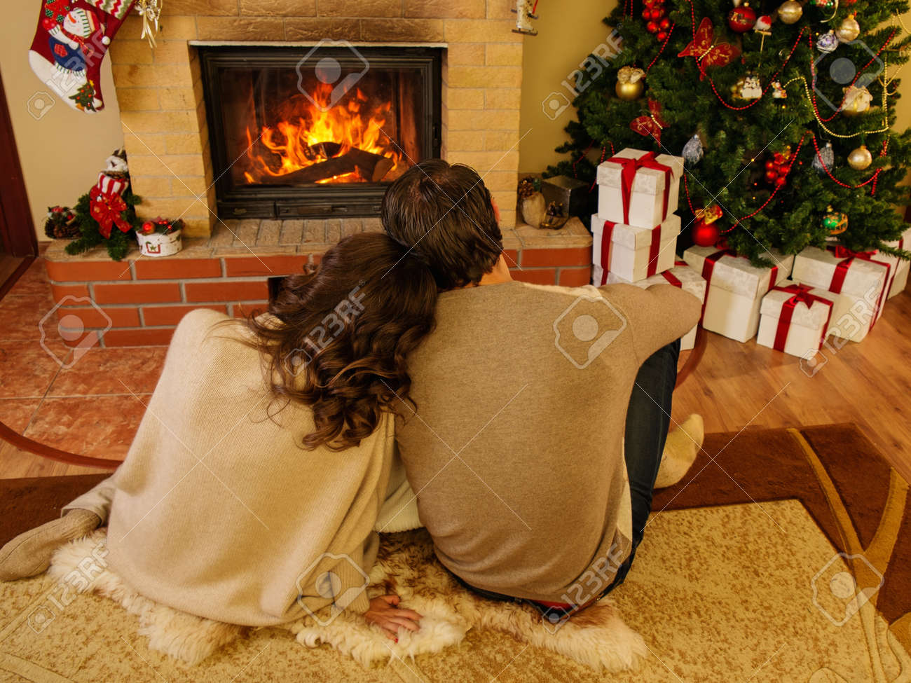 couple near fireplace in christmas decorated house interior stock