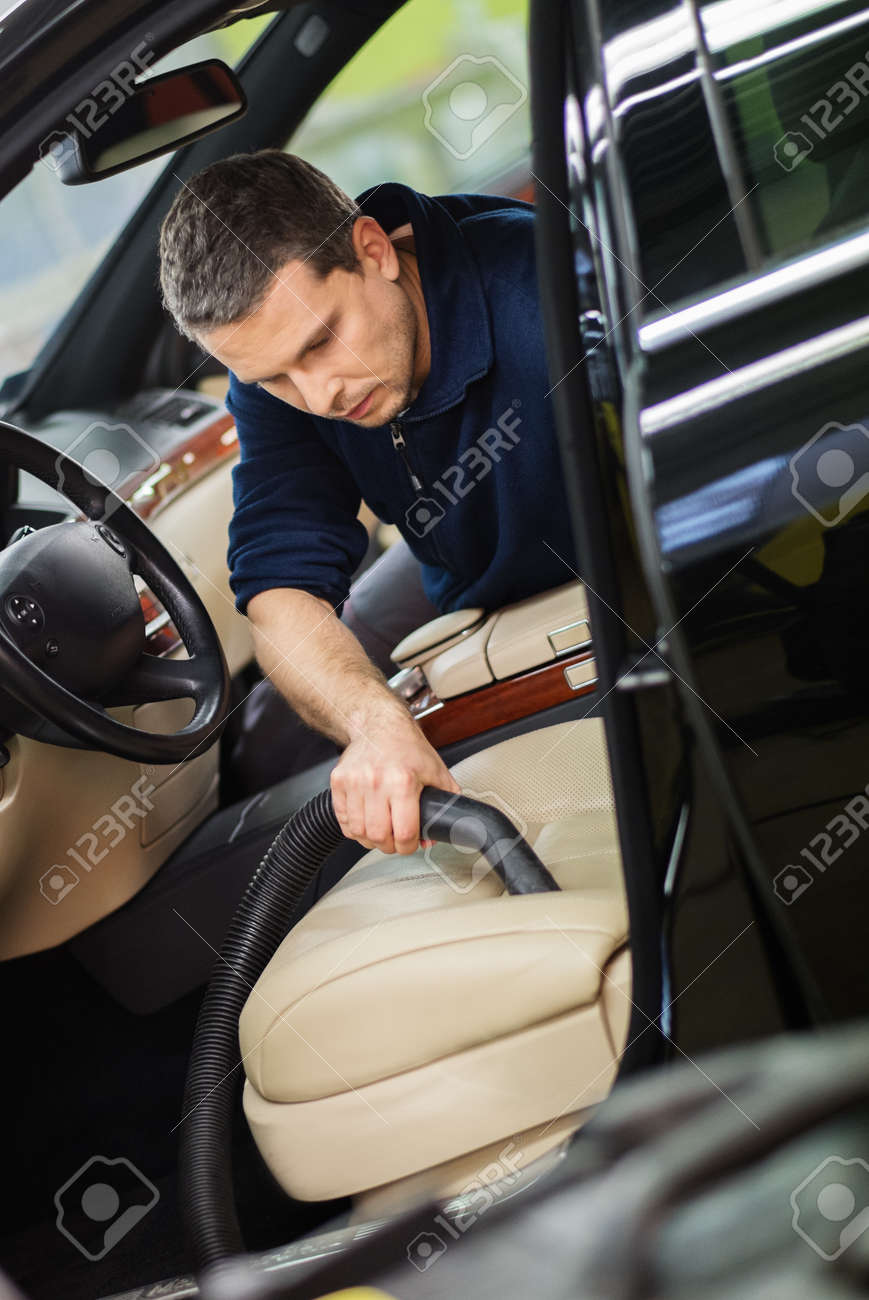 Stock Photo   Worker On A Car Wash Cleaning Car Interior With Vacuum Cleaner