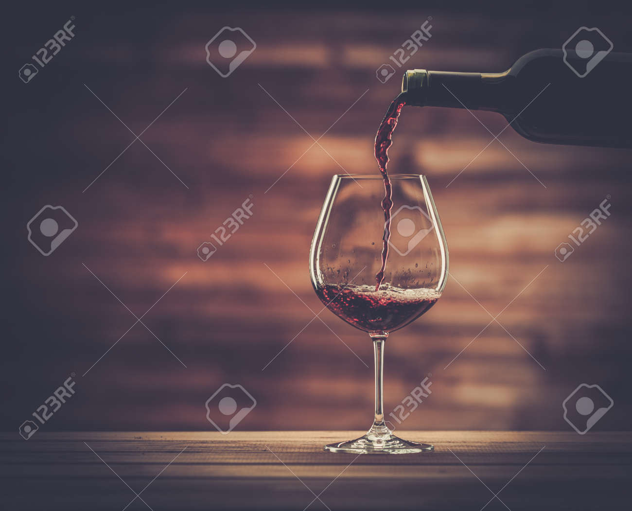 Pouring red wine into the glass against wooden background - 33958935