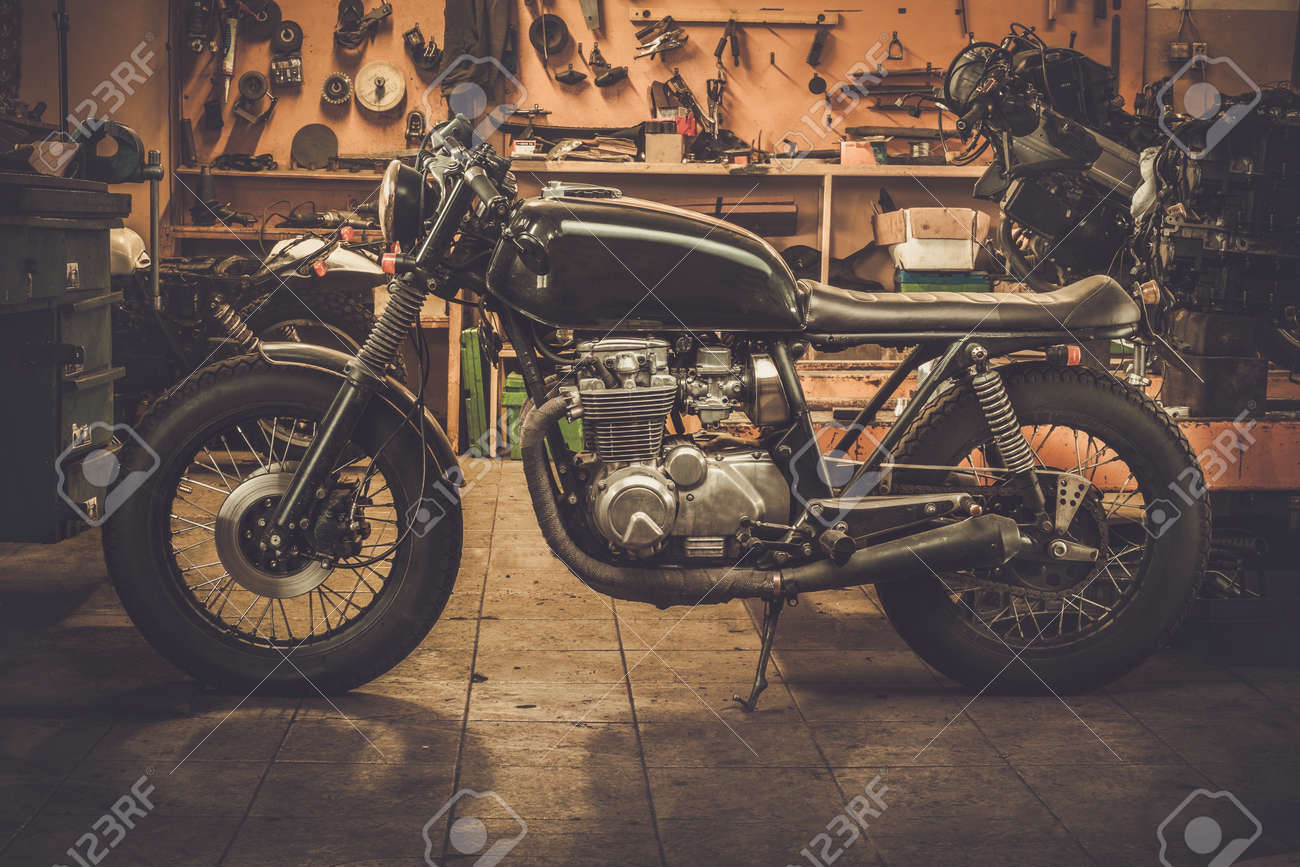 Vintage Style Cafe Racer Motorcycle In Customs Garage Stock Photo