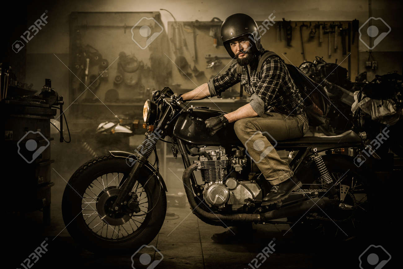 Rider And His Vintage Style Cafe Racer Motorcycle In Customs Garage Stock Photo