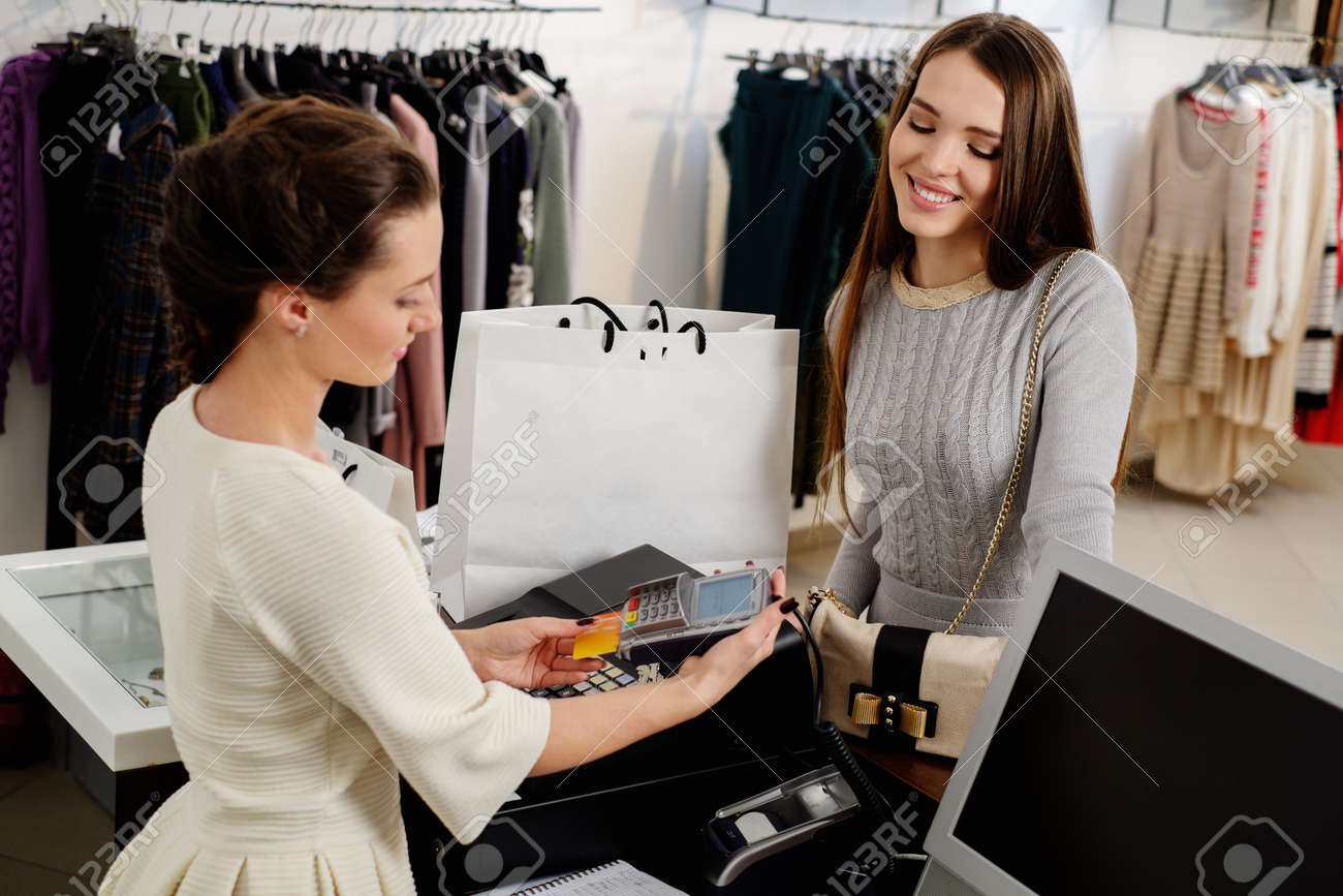 Happy woman customer paying with credit card in fashion showroom - 38653543