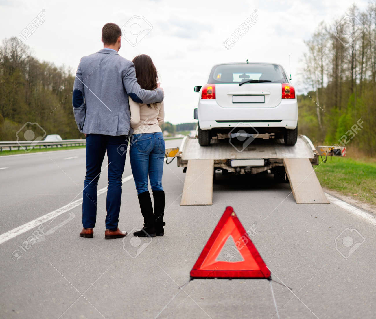 Couple near tow-truck picking up broken car - 39546097