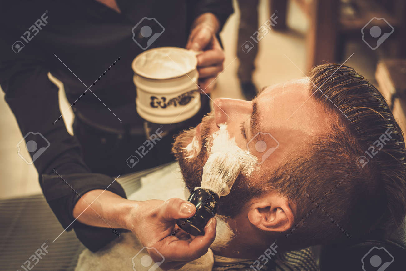 Client during beard shaving in barber shop - 42273624
