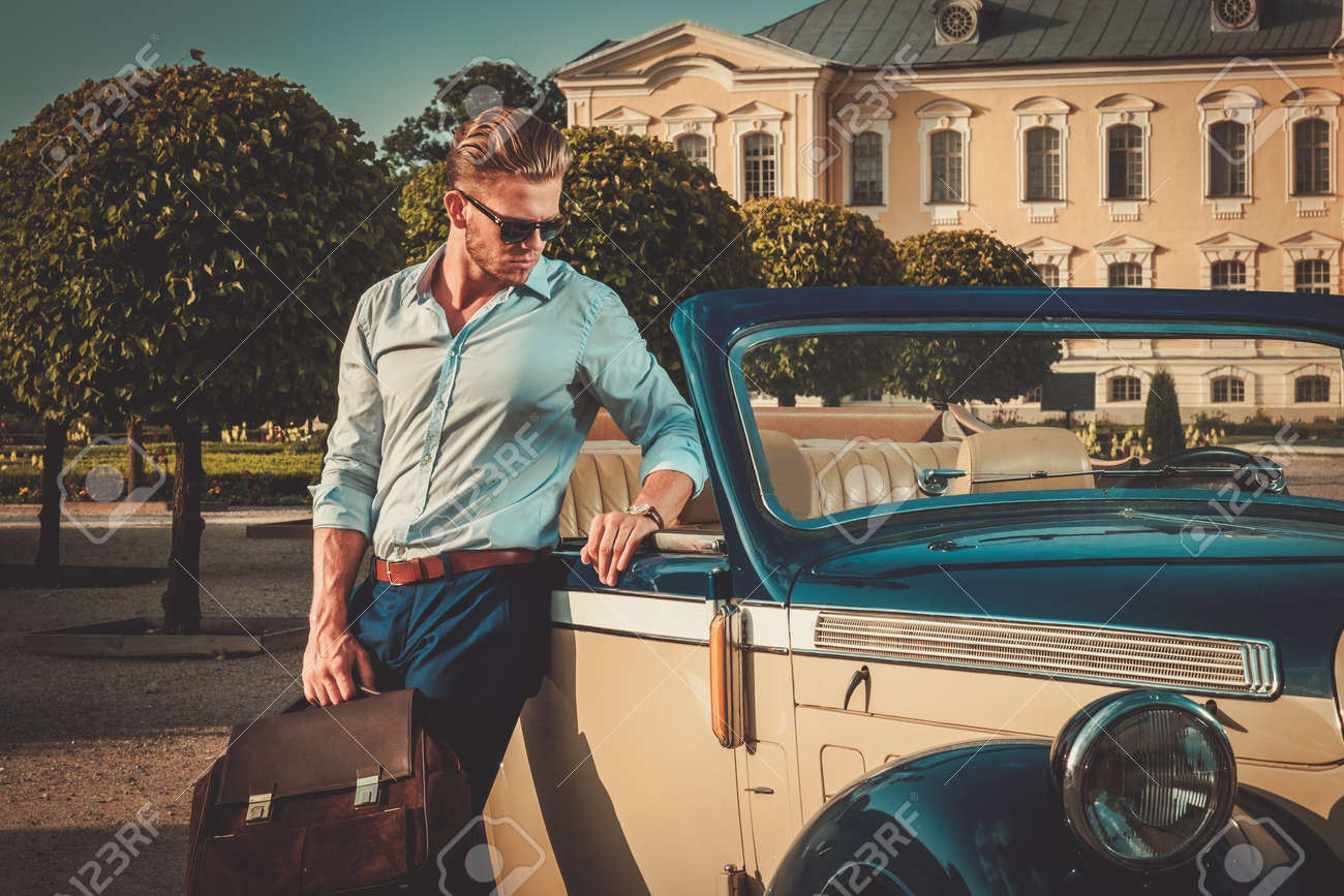 Confident wealthy young man with briefcase near classic convertible Stock Photo - 44959457