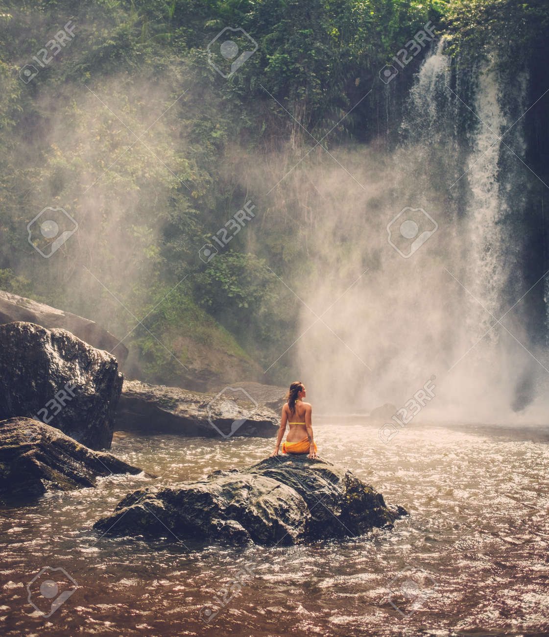 Beautiful woman sitting near waterfall enjoying the sun, Phnom Koulen at Siem Reap, Cambodia - 49591444