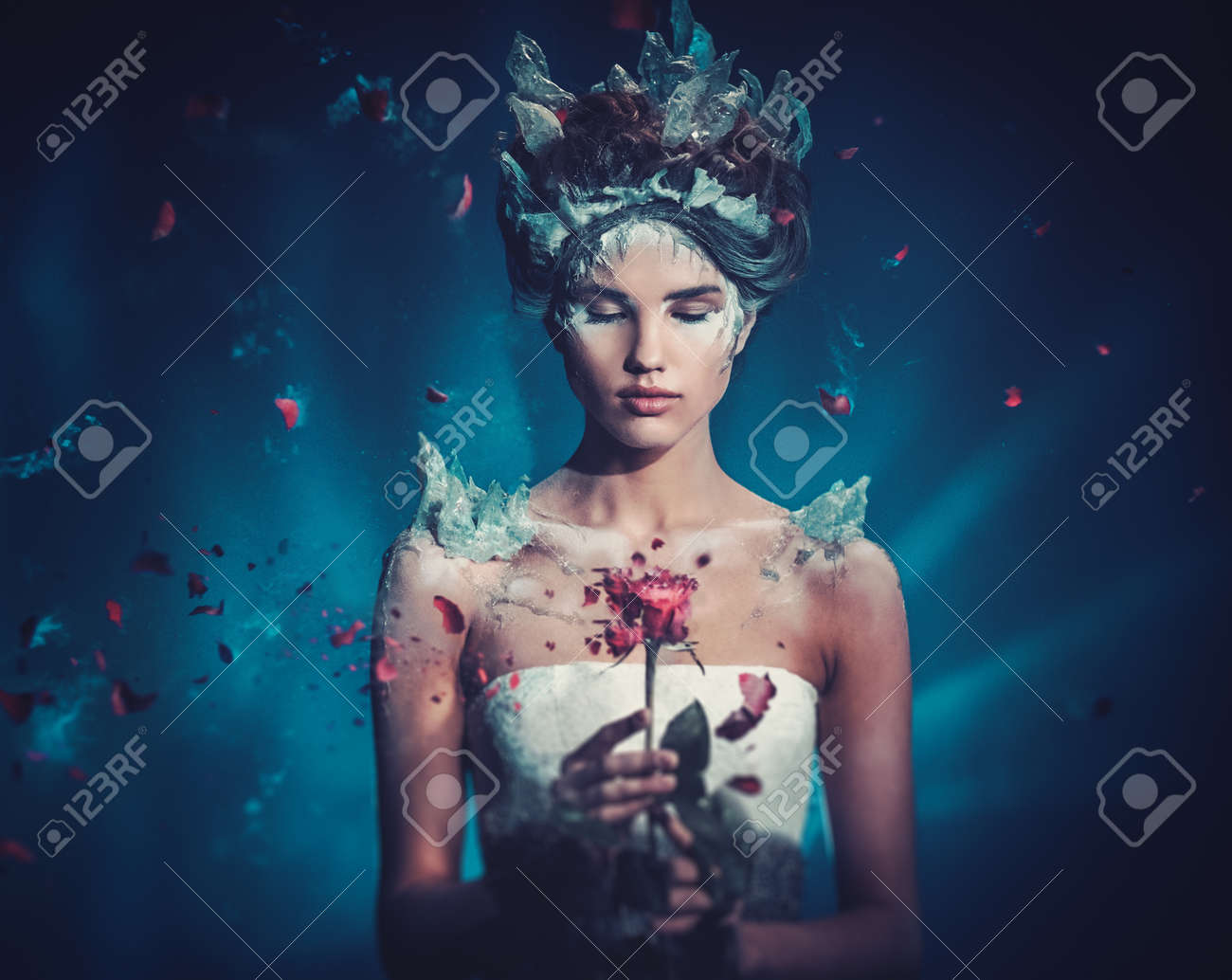 Winter beauty fantasy woman portrait. Beautiful young model girl and blast of frozen rose. Stock Photo - 50580716