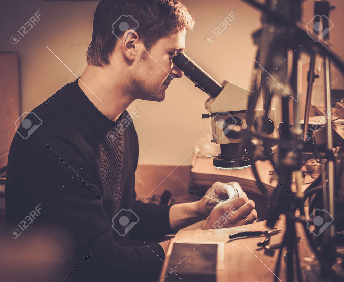 Jeweler looking at the ring through microscope in a workshop. Stock Photo - 50661938