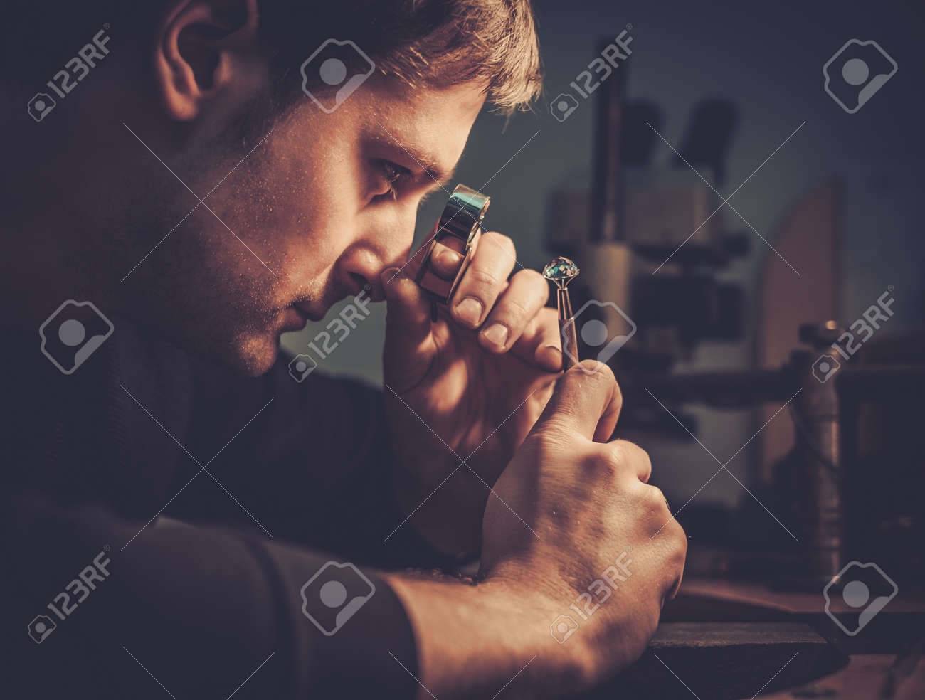 Jeweler looking at the ring through microscope in a workshop. Stock Photo - 50662043