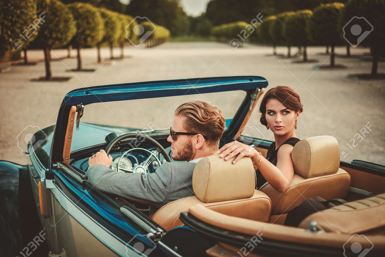 Wealthy couple in a classic convertible - 51338043