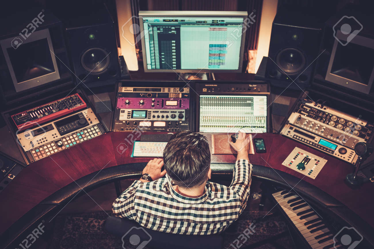 Sound engineer working at mixing panel in the boutique recording studio. Stock Photo - 51873574