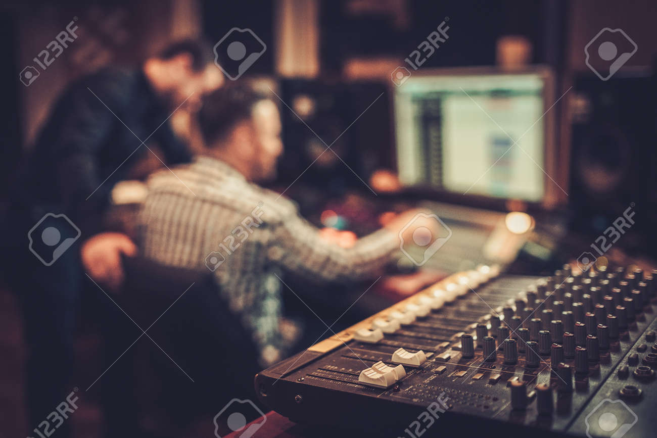 Sound engineer and producer working together at mixing panel in the boutique recording studio. - 51873437