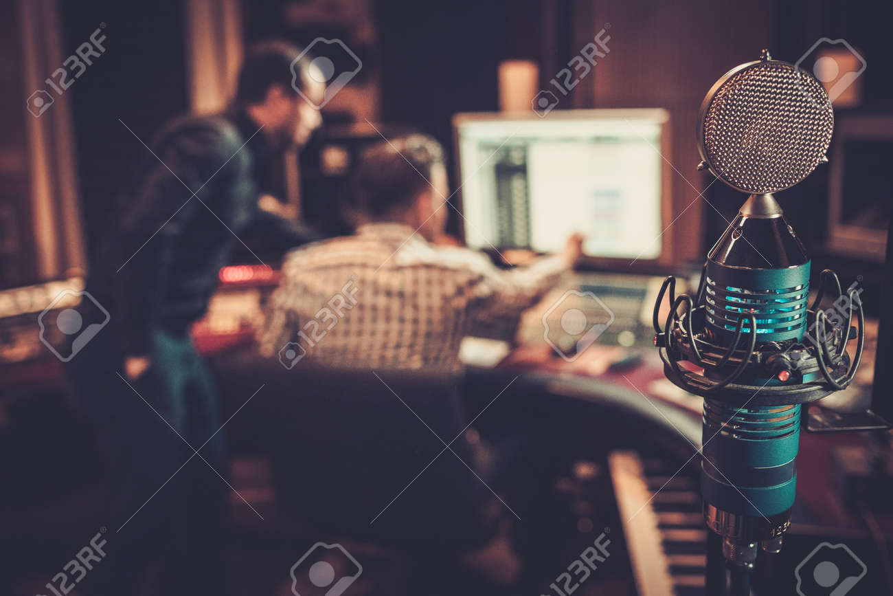 Sound engineer and producer working together at mixing panel in the boutique recording studio. Stock Photo - 51873278