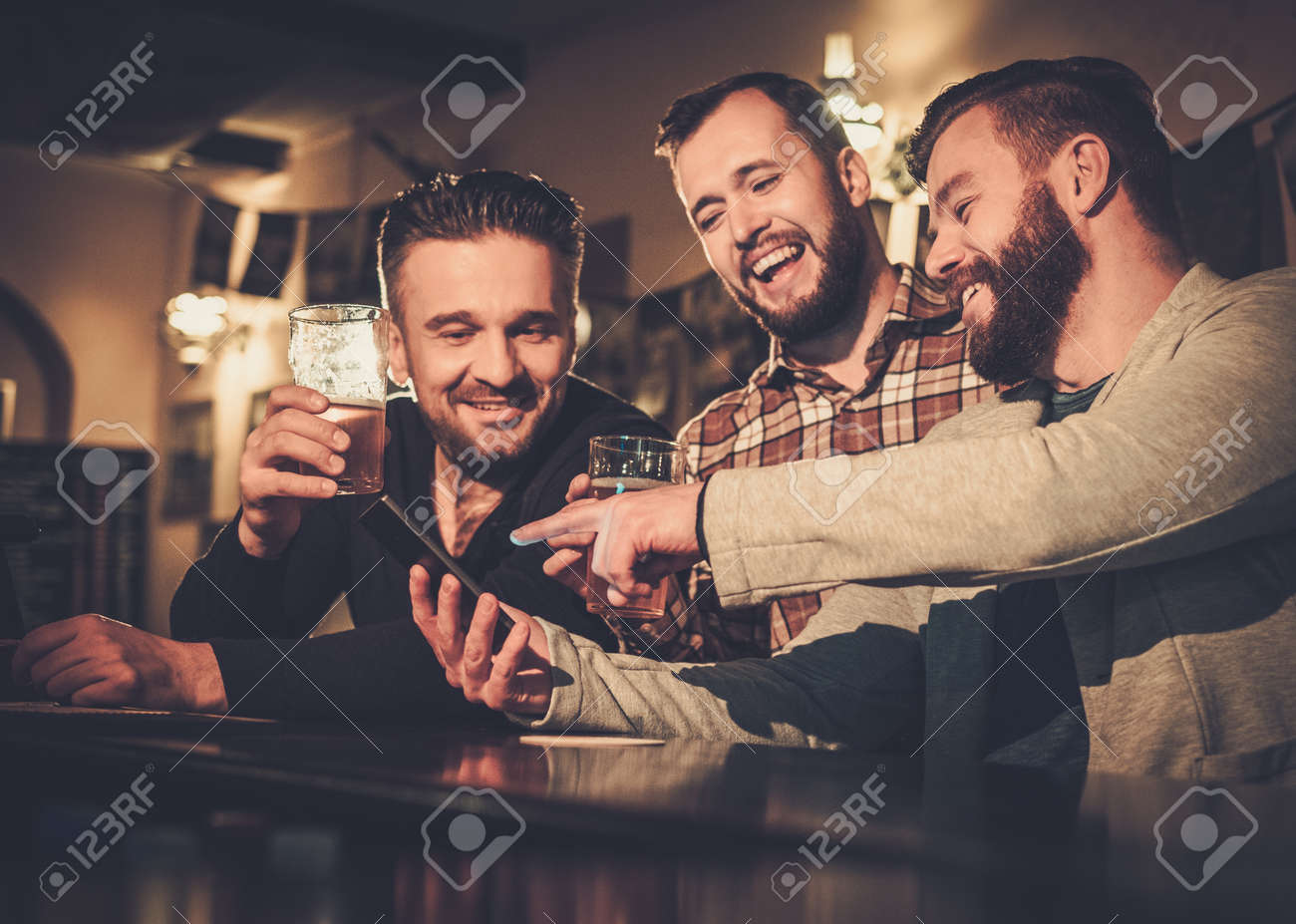 Cheerful old friends having fun with smartphone and drinking draft beer at bar counter in pub. Stock Photo - 53766592