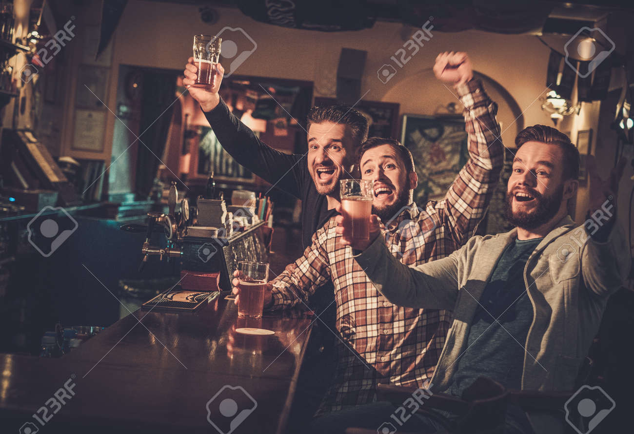 Cheerful old friends having fun watching a football game on TV and drinking draft beer at bar counter in pub. Stock Photo - 53766810