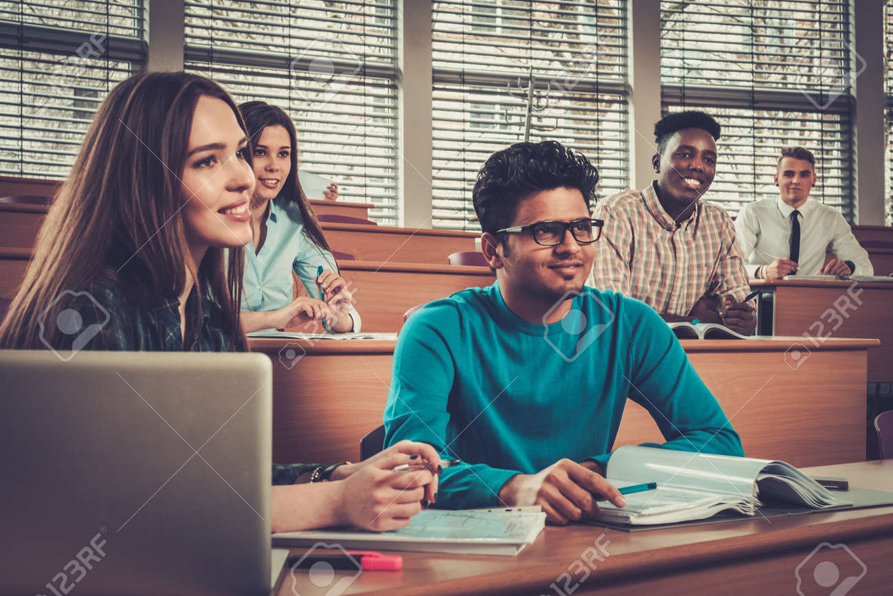 Multinational group of cheerful students taking an active part in a lesson while sitting in a lecture hall. Stock Photo - 53766949