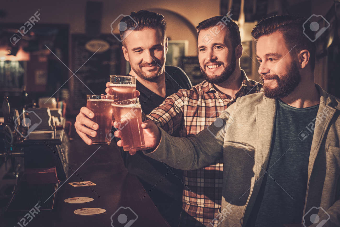 Cheerful old friends having fun and drinking draft beer at bar counter in pub. Stock Photo - 53766979