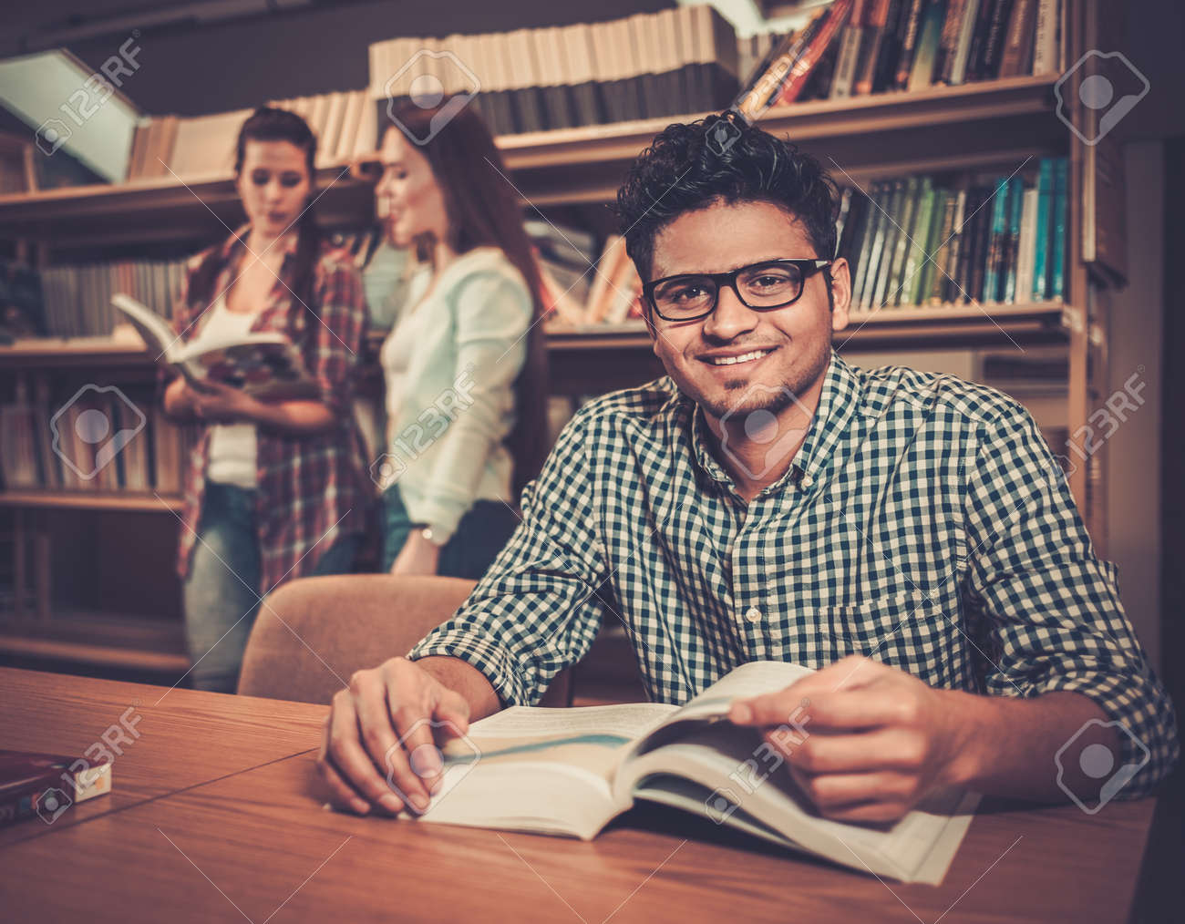 Multinational group of cheerful students studying in the university library. Stock Photo - 54363131