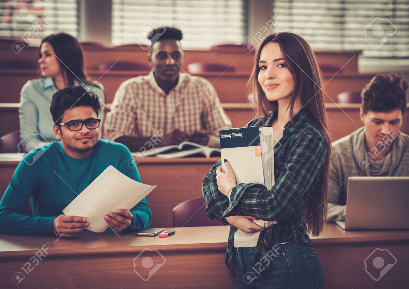 Multinational group of cheerful students taking an active part in a lesson while sitting in a lecture hall. Stock Photo - 54363032