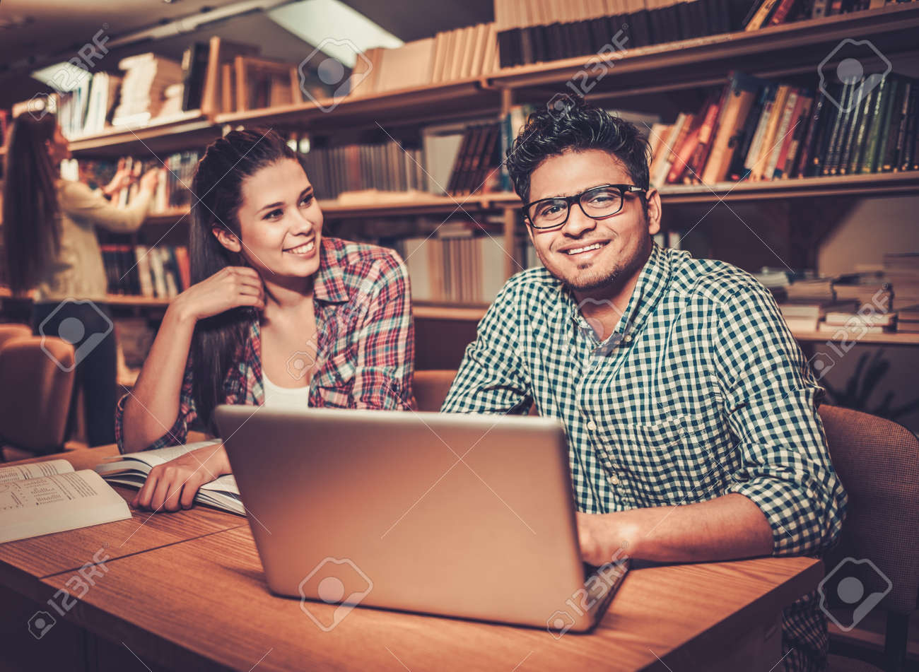 Multinational group of cheerful students studying in the university library. Stock Photo - 54362866
