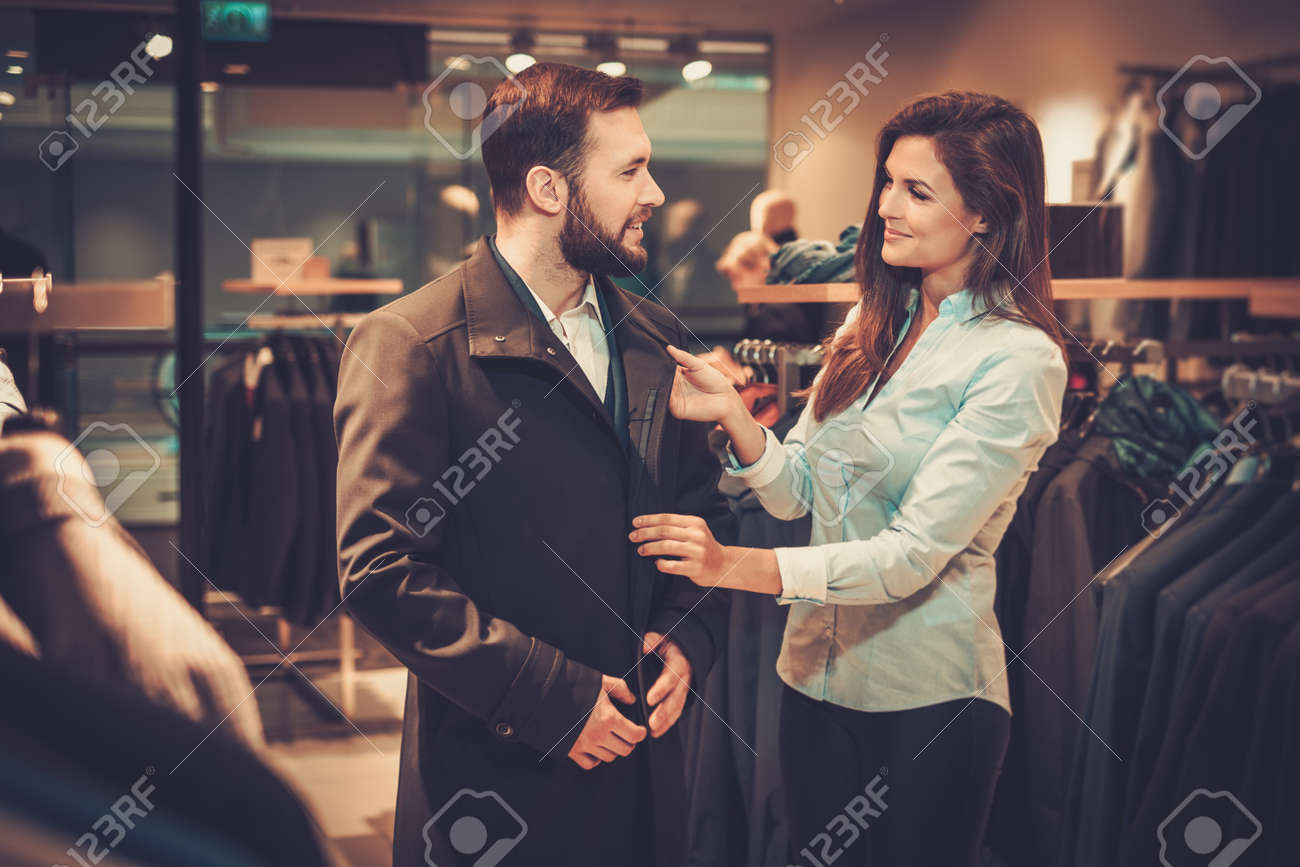 Confident handsome man with beard choosing a coat in a suit shop. Stock Photo - 54362615