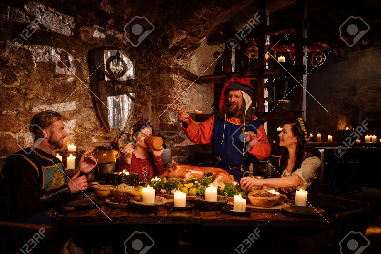 Medieval people eat and drink in ancient castle kitchen interior. Stock Photo - 56330229