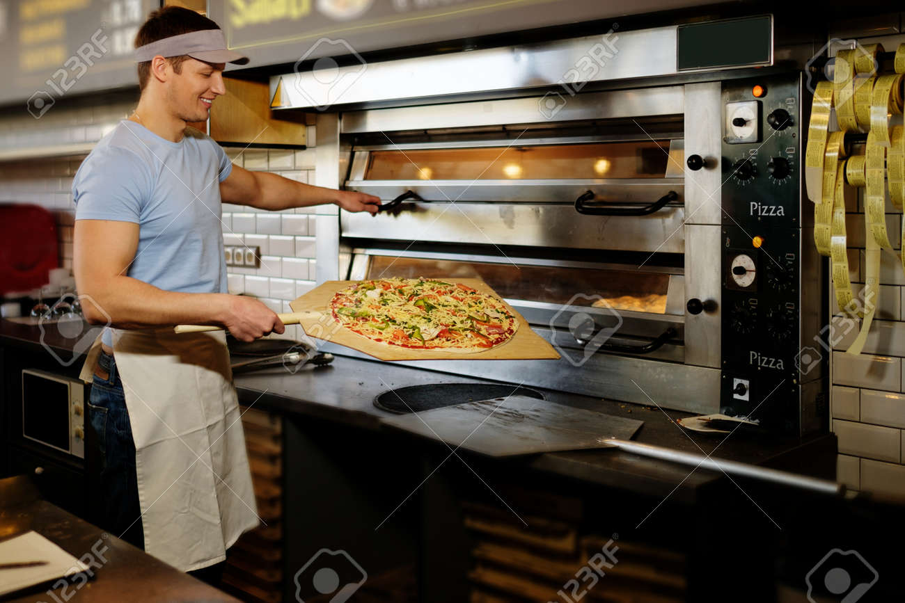Handsome pizzaiolo making pizza at kitchen in pizzeria. - 56713412