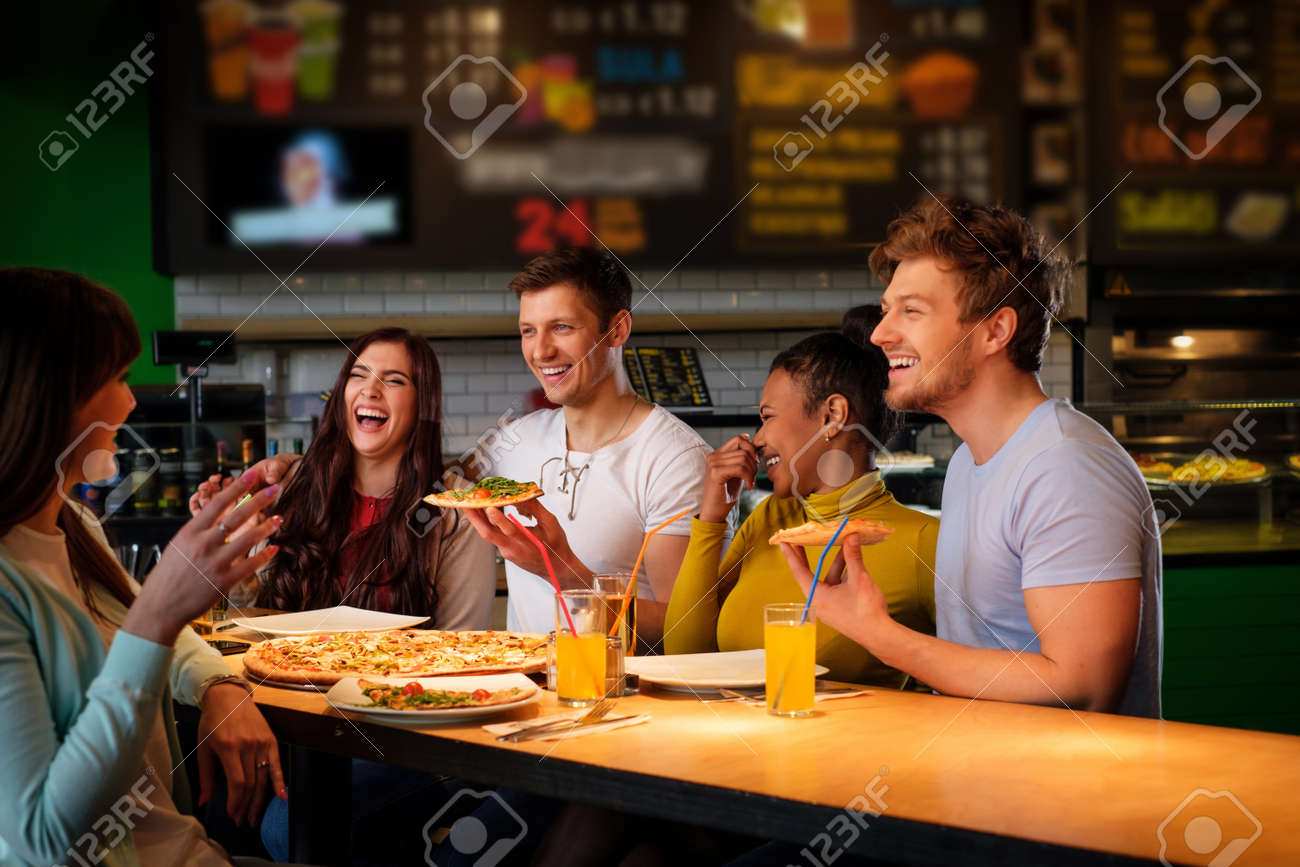 Cheerful multiracial friends having fun eating pizza in pizzeria. Stock Photo - 57069759