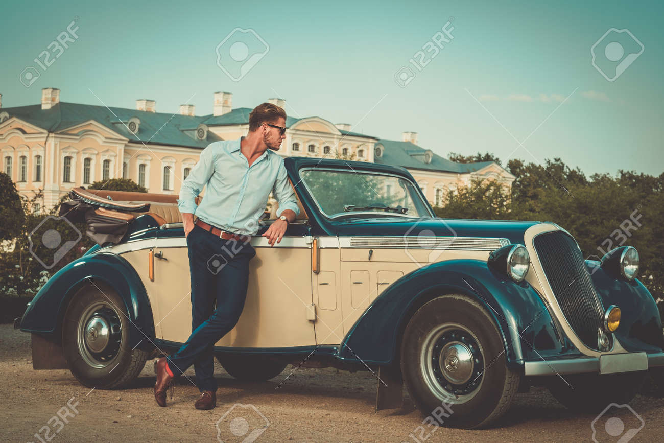 Confident wealthy young man near classic convertible - 57720845